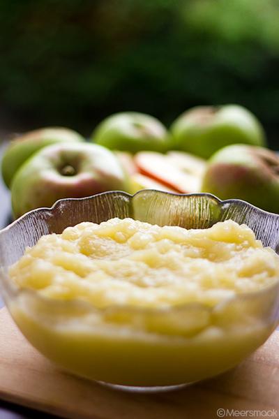 Appelmoes in een glazen kom appelen op de achtergrond.