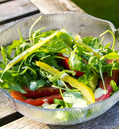 Salade, tomaat en paprika met dressing in een kom